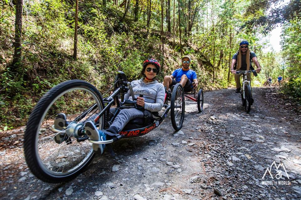 A disabled woman cycles in tandem with a partner on a leafy trail, with another bicyclist following behind.