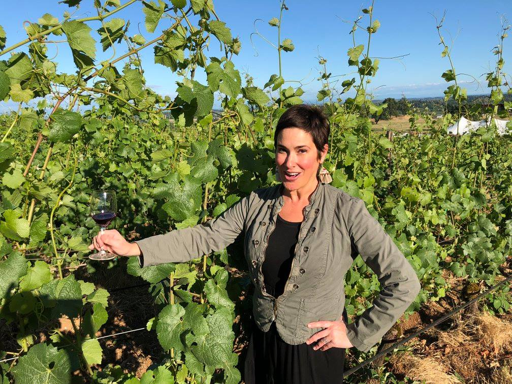 A woman with short dark hair standing on a sunny day among grape vines.