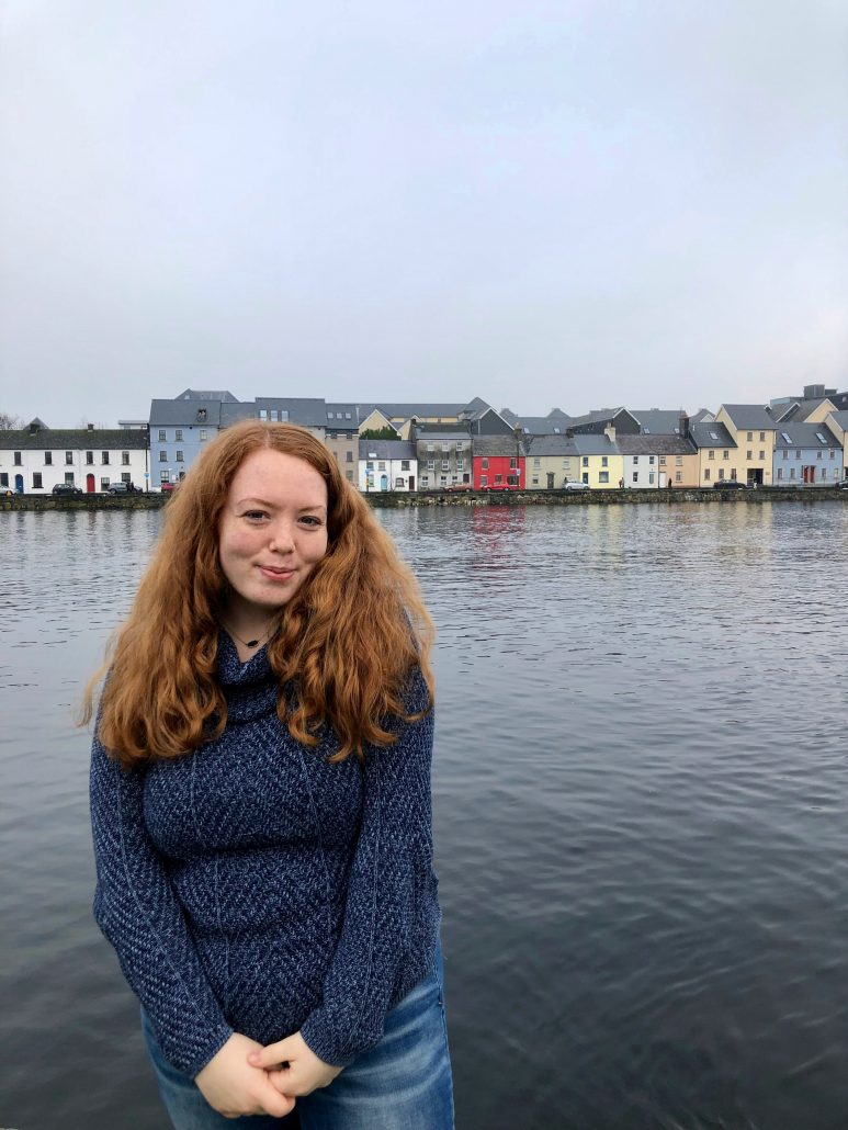 A freckled, ginger-haired girl stands in front of the water on a cloudy day wearing a blue sweater.