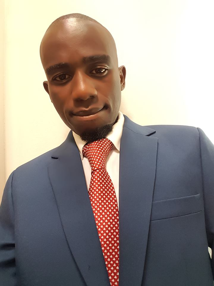 A handsome man from Zimbabwe wearing a blue suit, with a bald shaved head.