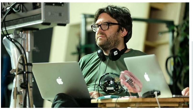 Actor Shaun Pye, a dark-haired actor in thick glasses sitting in front of two MacBook laptops.