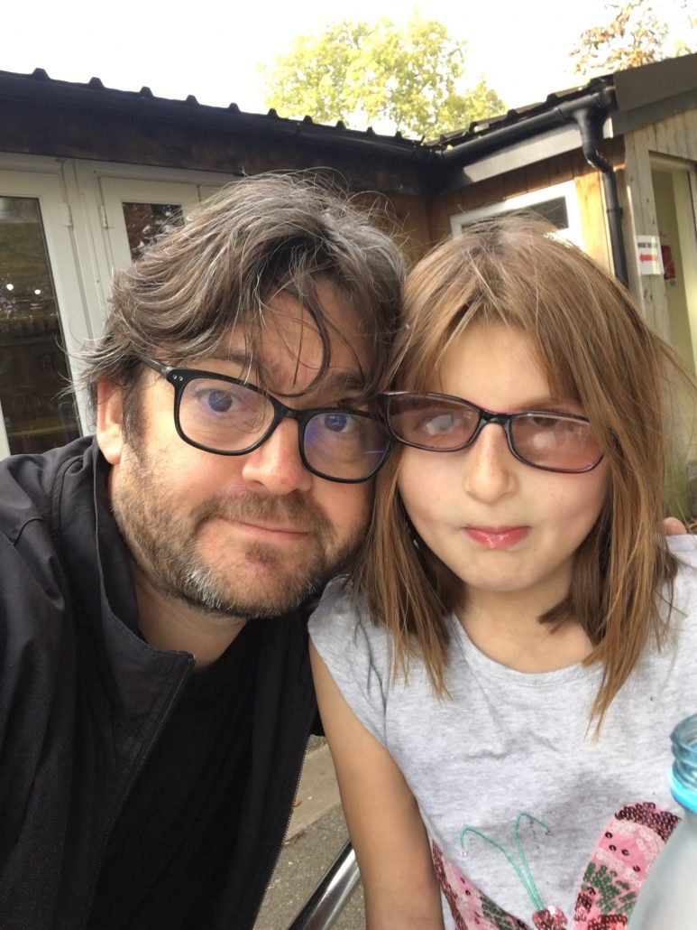 Comedian Shaun Pye wearing thick glasses standing next to his 12-year-old daughter, Joey, who also has large glasses.