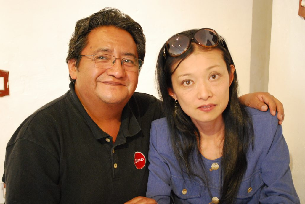 A friendly Mexican man with his arm around a blind Mexican-Japanese woman with sunglasses pushed up to her forehead.