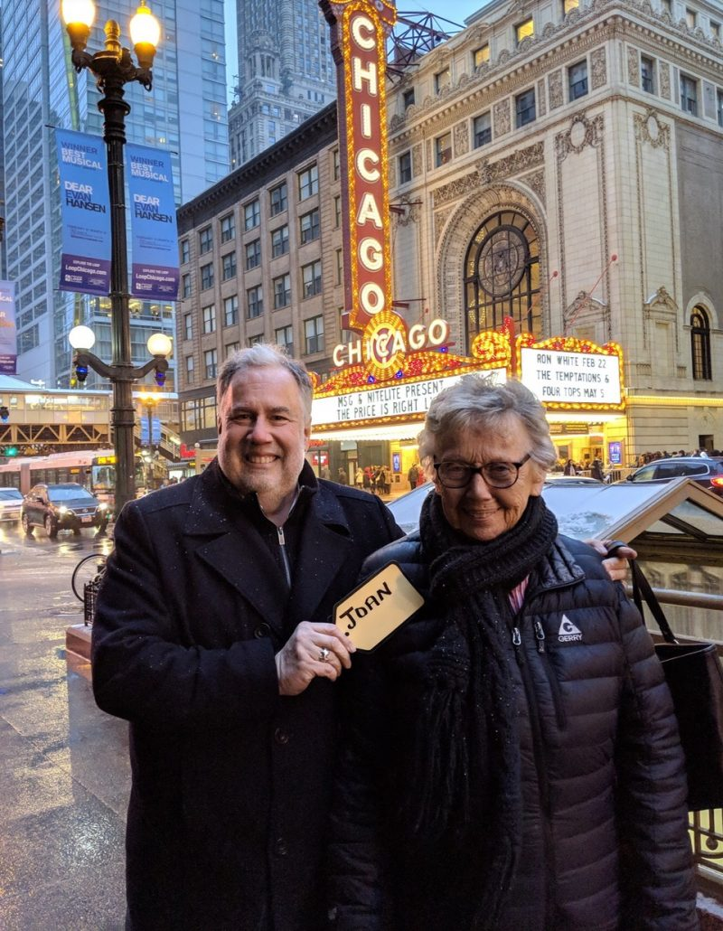 A middle-aged man and his mother stand outside of a theater, ready to go see Chicago.