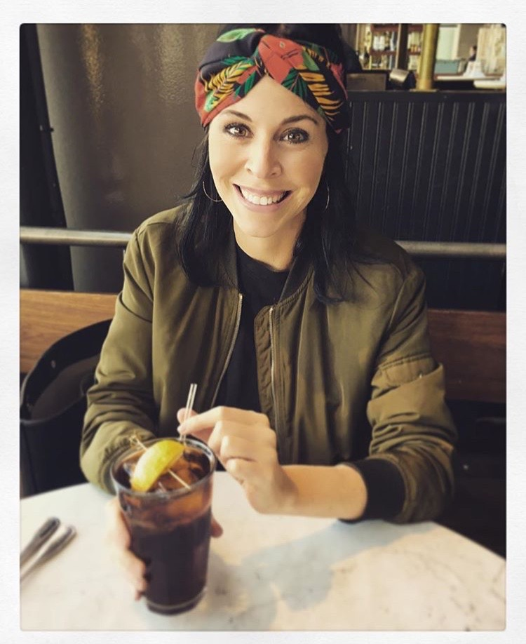 A pretty woman in her 40s with a head scarf sips a coke with lemon in it.