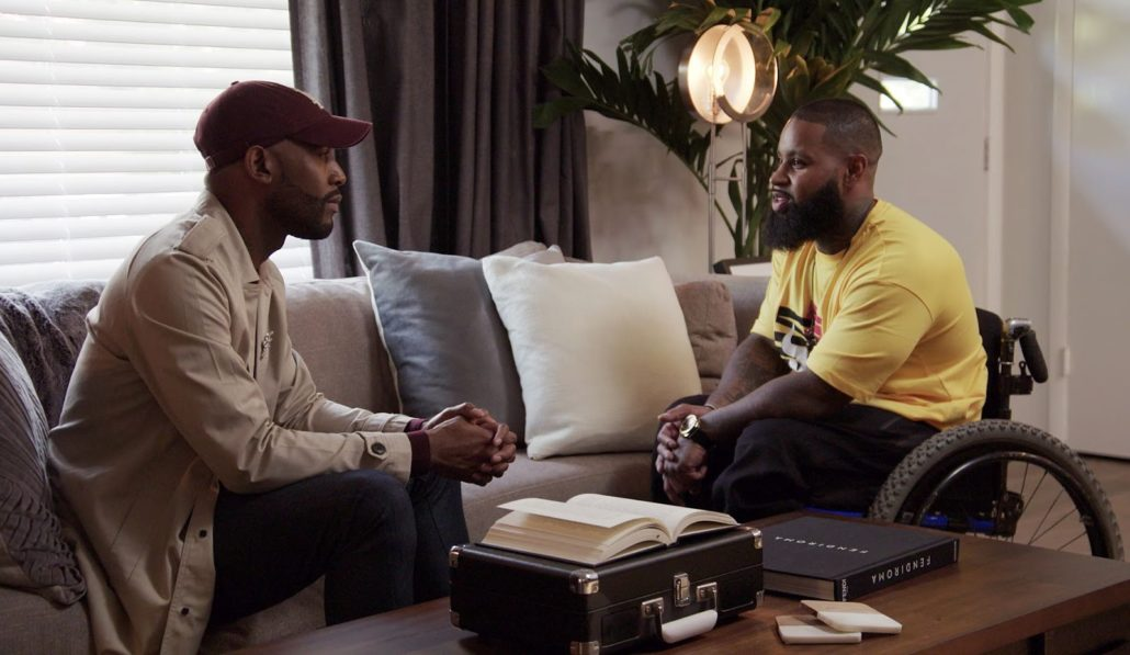A black man in a wheelchair consults with Karamo Brown, who is also African-American, on Netflix's Queer Eye television show.