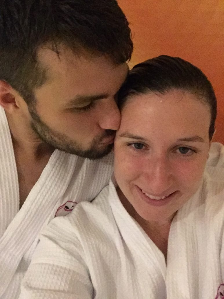 A man with a beard kissing a woman on the forehead, both wearing bath robes.