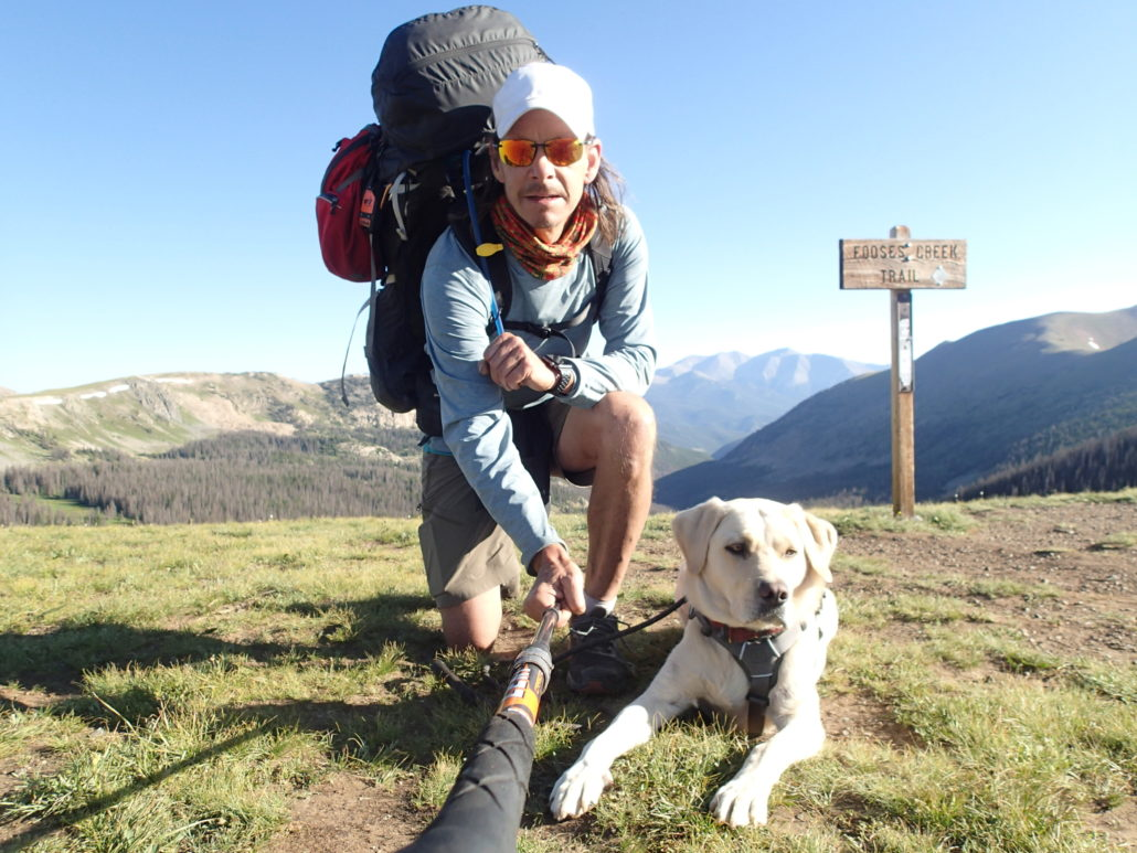 A hiker in Colorado posing for the camera with a white guide dog.